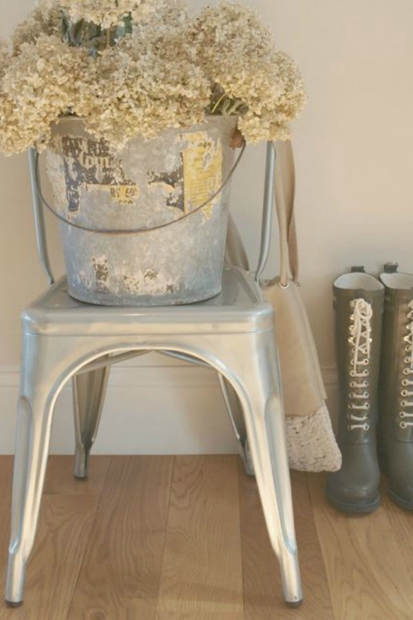 French metal bistro chair with vintage galvanized pail. Dried hydrangea and boots round out a French country vignete. Design by Hello Lovely Studio. #frenchcountry #tolixchair #bistrochair #hydrangea #vintagestyle #ilsejacobsen #galvanized #vintagepail
