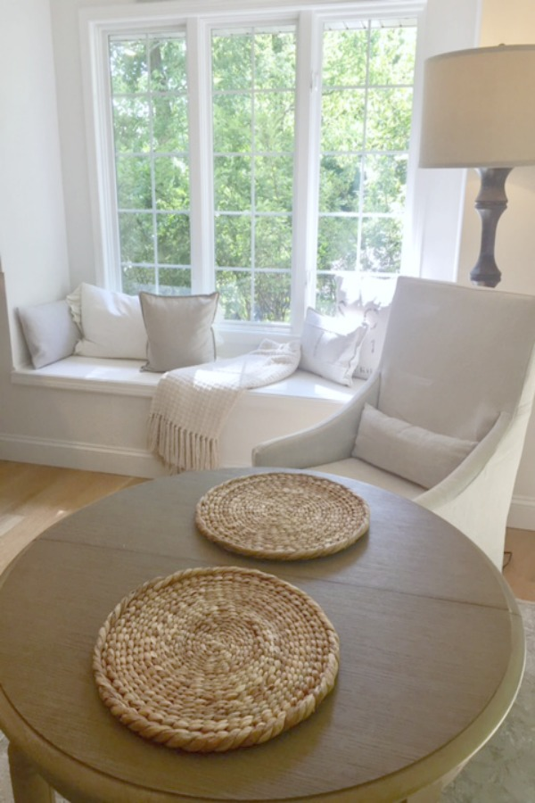 Our serene white kitchen with windowseat has a tranquil breakfast area with small round wood table, Belgian linen slipcovered armchairs, and floor lamp. #hellolovelystudio #serenekitchen #windowseat #europeanfarmhouse