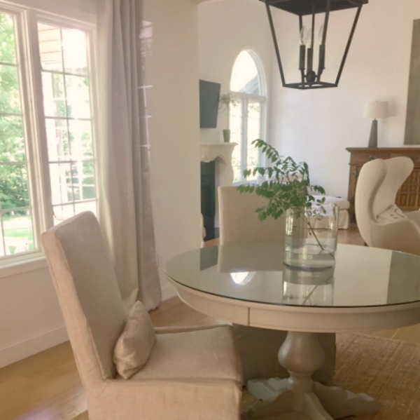 Dining room with Belgian linen slipcovered side chairs and round table. Carriage style lantern pendant over table. Hello Lovely Studio.
