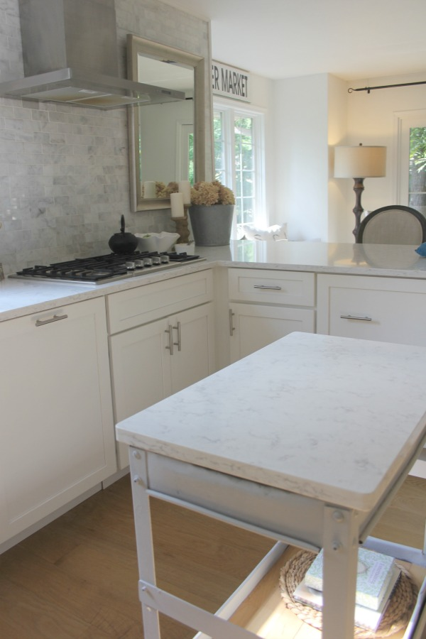 In our Lovely Tranquil Classic Kitchen is a mix of modern and vintage design elements. An industrial steel cart (painted Annie Sloan Paris Grey), Shaker cabinetry, marble subway tile backsplash, stainless pro appliances, fireclay farm sink, white oak hardwood flooring, and Viatera Minuet quartz on counters. #hellolovelystudio #whitekitchen #serenedecor #timelessdesign #modernfarmhouse #europeanfarmhouse #industrialcart #marblesubwaytile #whiteoak #viateraquartz #minuet #anniesloanparisgrey #steelcart