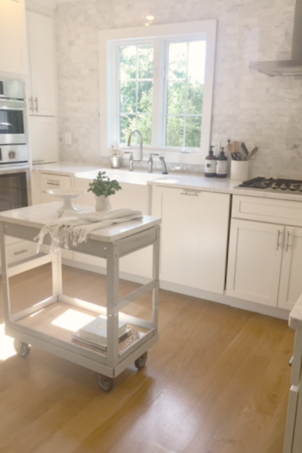 Industrial farmhouse cart in a serene white kitchen by Hello Lovely Studio. #hellolovelystudio #industrialcart #trolley #worktable