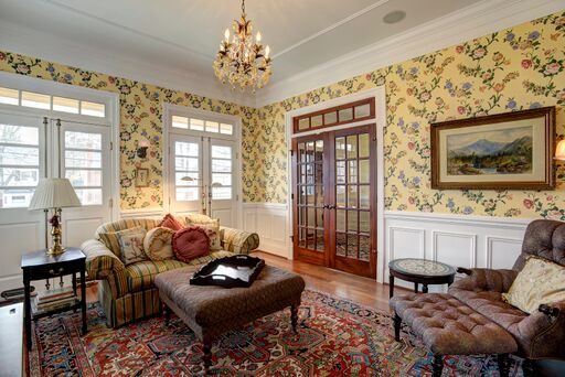 French country living room with yellow floral wallpaper, red oriental rug, and French doors with transom.