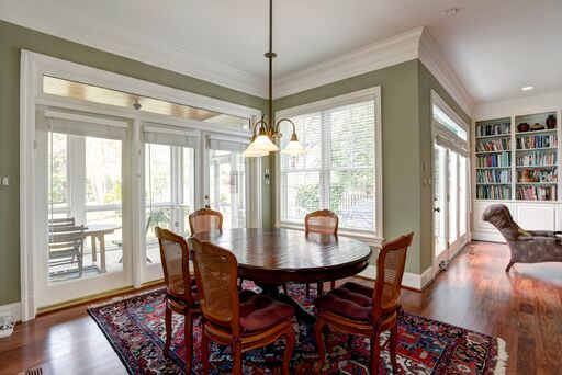 Traditional style breakfast room with sage green walls and red accents.