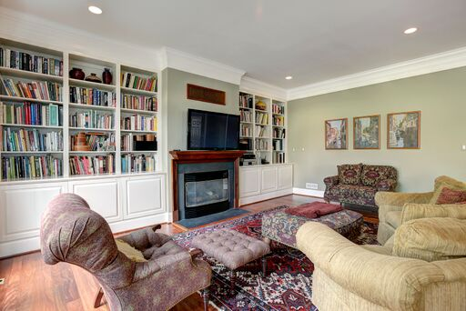 Traditional decor in a family room with sage green walls and built in bookcases.