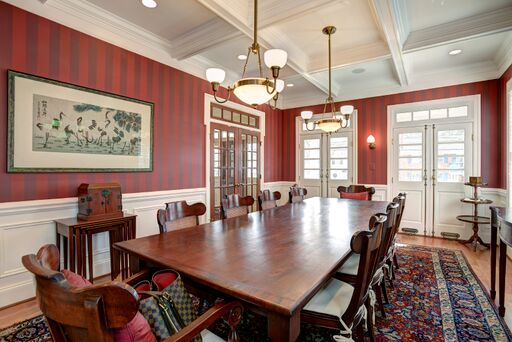 Red stripe wallpaper and decorative mouldings in French country dining room.