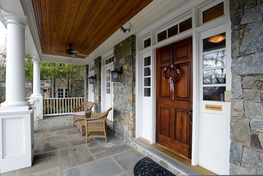 Front porch of stone Colonial house with columns, wood ceiling, and beautiful stone porch floor.
