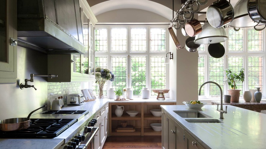 New England style coastal kitchen design by Artichoke and Michael Smith. The pot rack above the island resolved a lighting issue. #bespoke #kitchendesign #artichoke #coastalkitchen #newengland