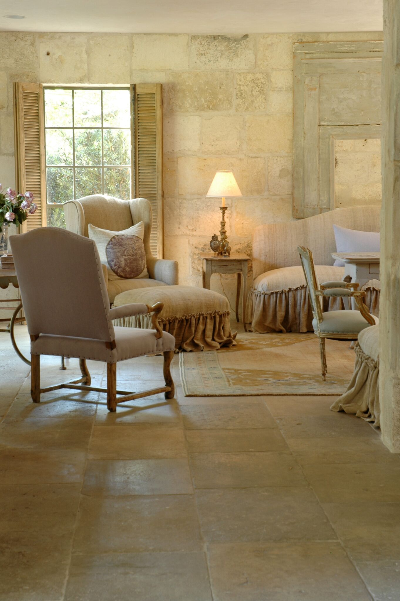 French country living room with reclaimed antique stone floors and walls. Chateau Domingue. Design by Pamela Pierce.
