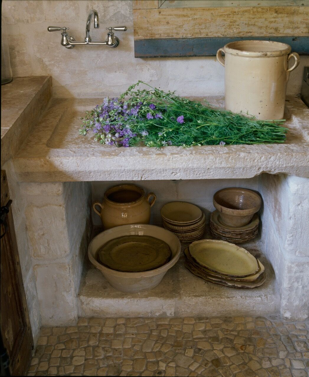 Ancient stone sink in a beautiful kitchen with reclaimed materials sourced in France and Europe - Chateau Domingue.