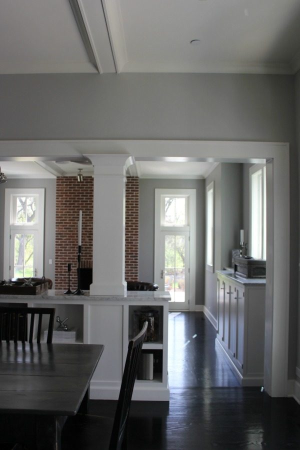 Architectural details are grand in a restored 1875 farmhouse kitchen and family room. Score the exact medium grey paint colors on Hello Lovely. #interiordesign #industrialfarmhouse #benjaminmoorestoningtongray #farmhousearchitecture #blackfloors