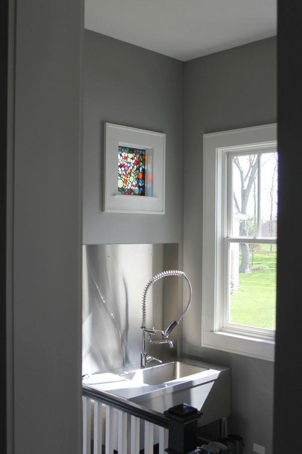 Mud room in a modern farmhouse with Benjamin Moore Stonington Gray walls, stainless steel, and a stained glass window. #benjaminmoorestoningtongray #paintcolors #interiordesign #mudroom
