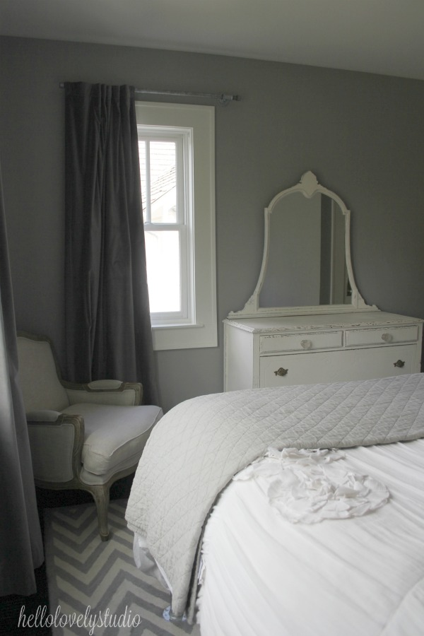 Farmhouse style bedroom with vintage whit dresser, European linen arm chair, and herringbone area rug. Paint color on walls is Benjamin Moore Stonington Gray. #hellolovelystudio #farmhousebedroom #shabbychic #benjaminmoorestoningtongray