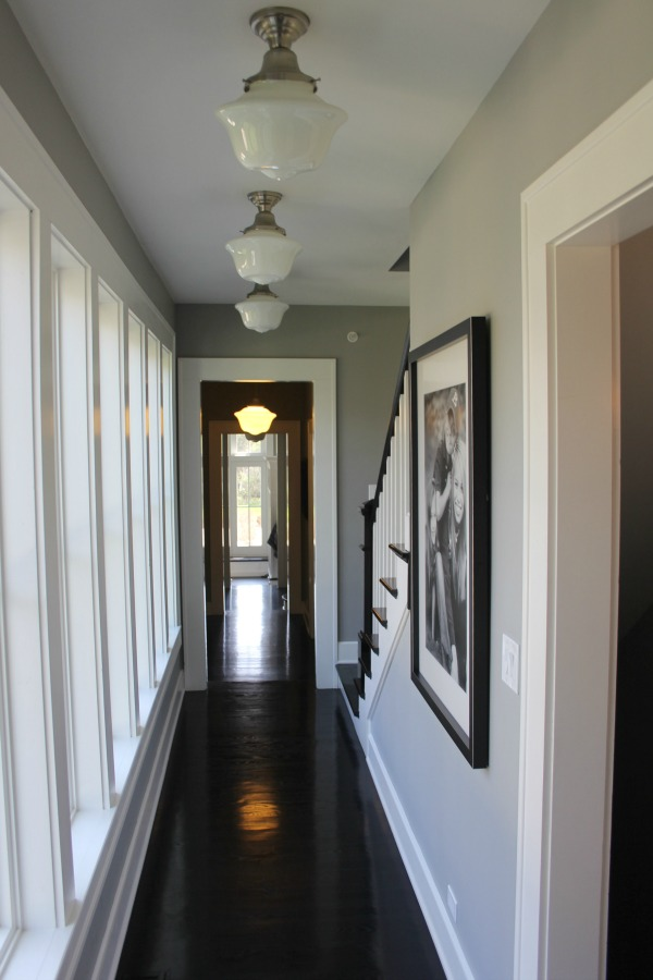 Reflective black flooring in a hallway with schoolhouse lights and medium grey paint colors. Come score the exact colors used on Hello Lovely. #interiordesign #greypaint #paintcolors #blackfloors #industrialfarmhouse