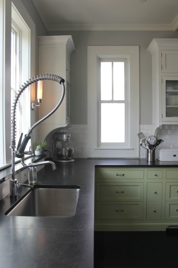 Custom green base cabinets in a charming farmhouse kitchen with medium grey paint colors. Farmhouse interior design inspiration for fans of industrial, modern, and traditional farmhouse house designs.  #interiordesign #indusrialfarmhouse #kitchen #paintcolor