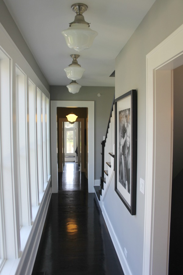 Black hardwood flooring in a hallway of a historic farmhouse with school house lights and grey painted walls. Paint color is Benjamin Moore Stonington Gray. #benjaminmoorestoningtongray #wallcolor #hallway #blackfloors #farmhouse #interiordesign #schoolhouselighting