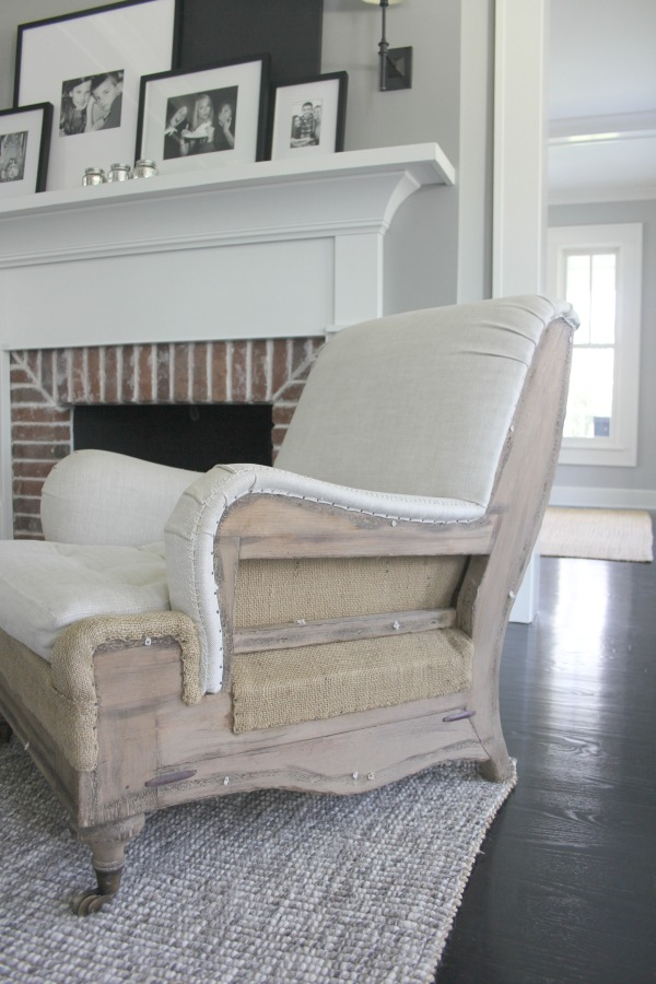 A deconstructed arm chair in a living room. Farmhouse interior design inspiration for fans of industrial, modern, and traditional farmhouse house designs. This 1875 historical farmhouse in Barrington, Illinois was renovated to a high standard with superior craftsmanship and bespoke design details. Score medium grey paint colors and ideas for decorating. #industrialfarmhouse #greypaint