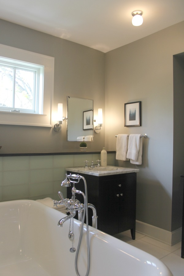 Traditional style bathroom with freestanding Waterworks tub, black vanity with carrara marble, and glass tile backsplash. #hellolovelystudio #bathroomdesign #freestandingtub #blackvanity #greywalls #benjaminmoorestoningtongray