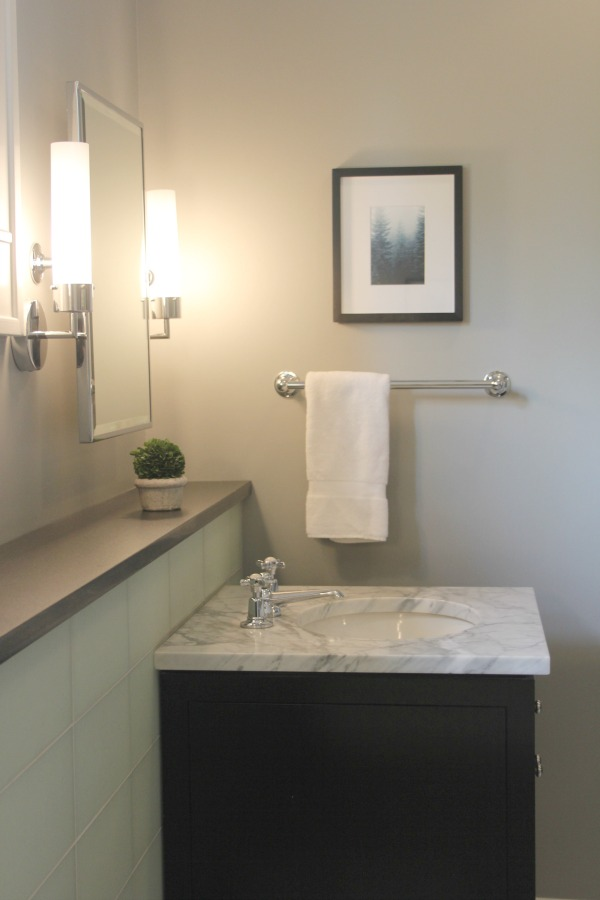 Benjamin Moore Stonington Gray in a luxurious bathroom with glass tile and black vanity. #hellolovelystudio #bathroomdesign #benjaminmoore #stoningtongray #greywalls #luxurybathroom