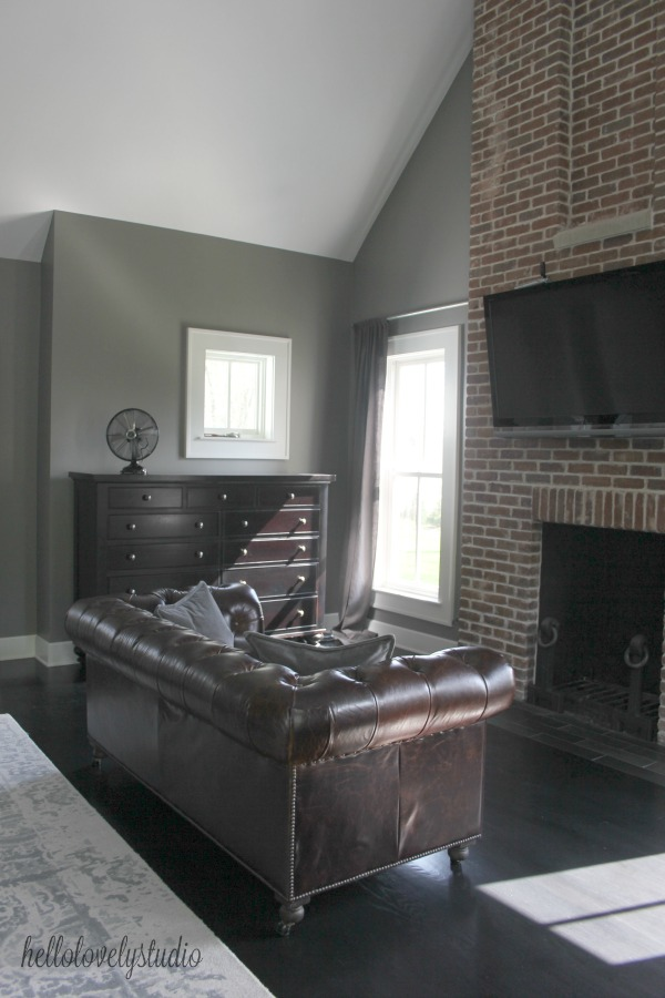 Benjamin Moore Platinum Gray paint on walls in a modern farmhouse bedroom with leather Chesterfield sofa and red brick fireplace.Time to Paint Your Walls? Come discover a Refresher to Demystify the Process!