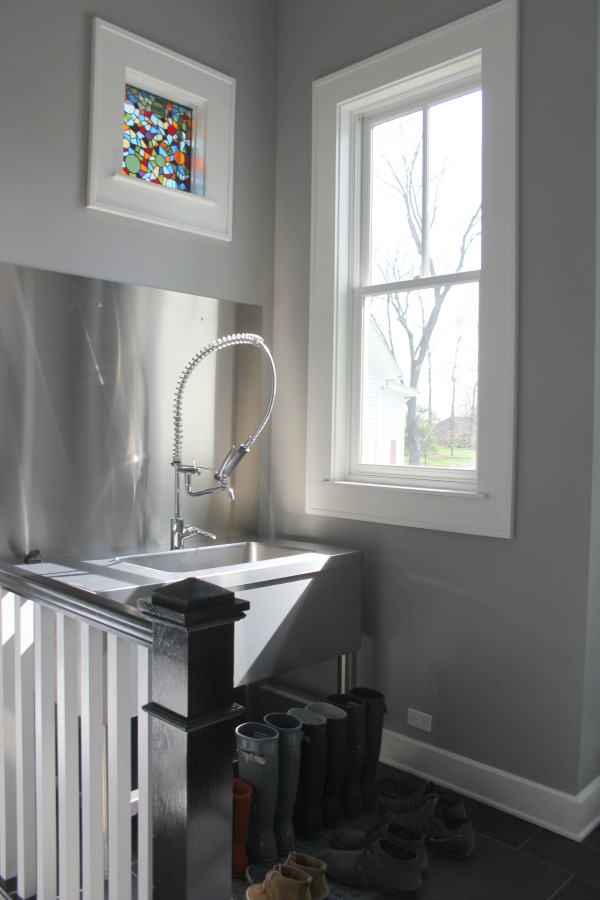 Mud room with stainless steel and an industrial sink with sprayer. Farmhouse interior design inspiration for fans of industrial, modern, and traditional farmhouse house designs. This 1875 historical farmhouse in Barrington, Illinois was renovated to a high standard with superior craftsmanship and bespoke design details. Come get the medium grey paint colors used here. #greypaint #mudroom #interiordesign #paintcolors