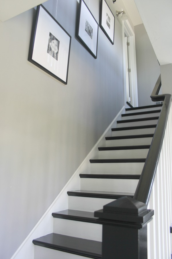 Black painted stairs, grey walls, and white painted stair risers. Farmhouse interior design inspiration for fans of industrial, modern, and traditional farmhouse house designs. This 1875 historical farmhouse in Barrington, Illinois was renovated to a high standard with superior craftsmanship and bespoke design details. Come score ideas for medium grey paint colors on Hello Lovely. #staircase #blackfloors #greypaintcolors