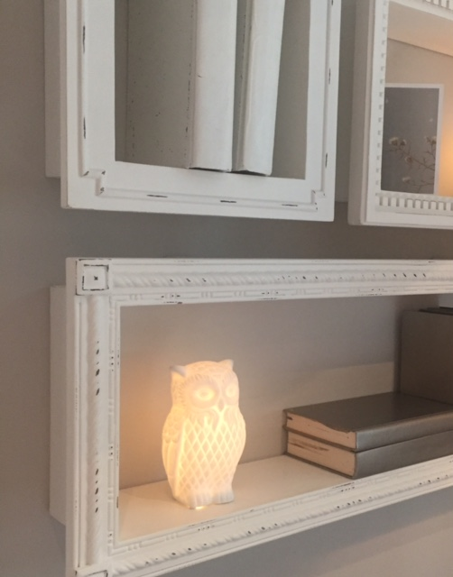 Vintage style shelves with mixmatched frames on wall. Owl nightlight. RH Chicago.