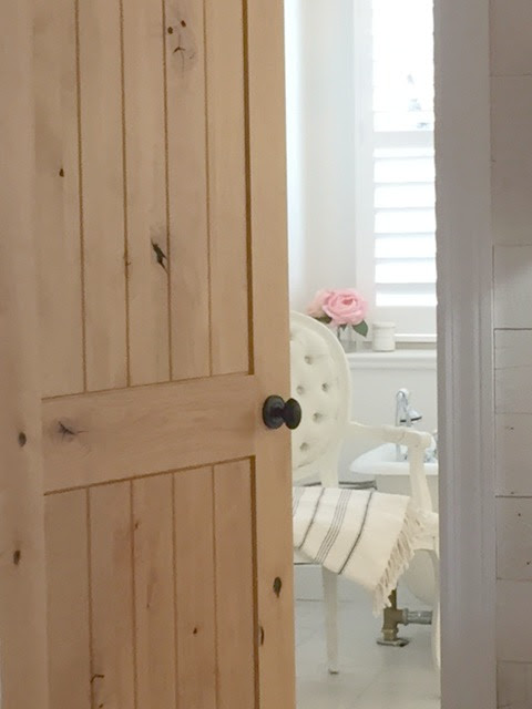 Knotty alder door to a white French country style bathroom. Hello Lovely Studio.