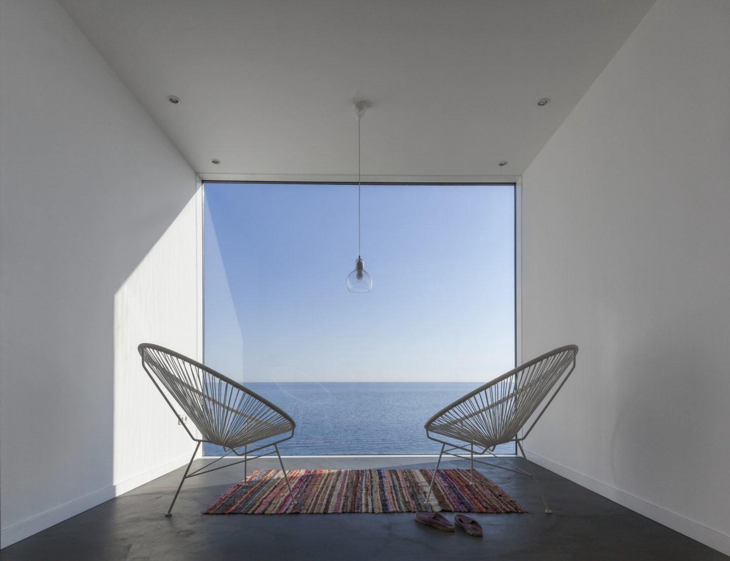 Two modern wire chairs in a small space overlooking the ocean. A wall of glass provides an unobstructed view. #beachhouse #oceanfront #modernarchitecture #wallofglass