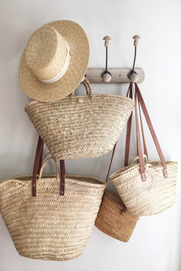 Charming French market baskets from Vivi et Margot hang from a hook in a charming farmhouse in France. Get the paint colors and design resources now!#vivietmargot #frenchmakret #frenchbaskets #marketbaskets #summerliving #rusticdecor #frenchcountry