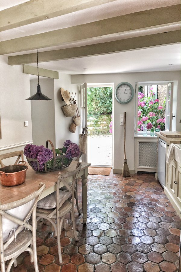 An authentically renovated French farmhouse kitchen near Bordeaux, France, by Vivi et Margot features reclaimed terracotta hex tile floors, rustic ceiling beams, and a custom kitchen by Neptune. Click through for Perfect Light Gray Paint Colors You'll Love as Well as Interior Design Inspiration Photos. #bestgreypaint #paintcolors