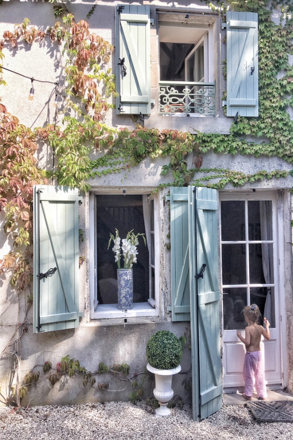 Green shutters and climbing vines on a breathtaking French farmhouse exterior. Vivi et Margot! Come be inspired by this house tour on Hello Lovely. #vivietmargo #frenchfarmhouse #climbingvines #exterior #greenshutters #vertolivier #romanticdecor #frenchcountry #europeanfarmhouse