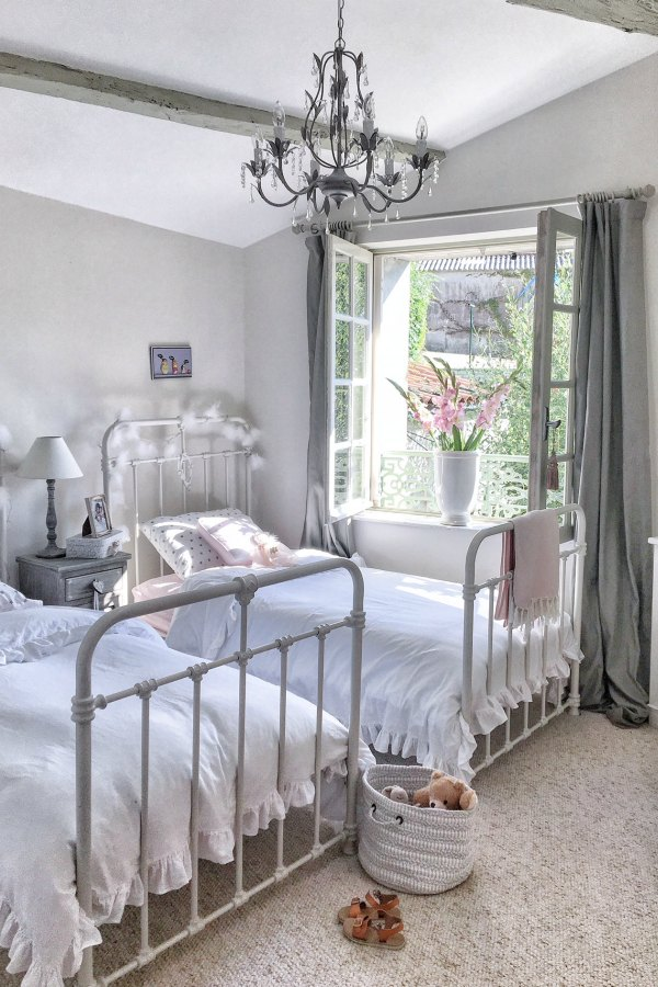 Serene, quiet, and timeless, this girls bedroom in a French farmhouse has ancient windows allowing the fresh air in, Farrow and Ball Strong White paint color on the walls, and pink accents from Pottery Barn. Vivi et Margot.