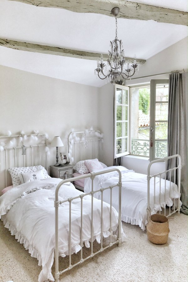 Beautiful French farmhouse bedroom with vintage style iron beds, rustic wood beams, and chandelier. Vivi et Margot. Photo by Charlotte Reiss. #vivietmargot #frenchfarmhouse #bedroom #frenchbedroom #farmhousebedroom
