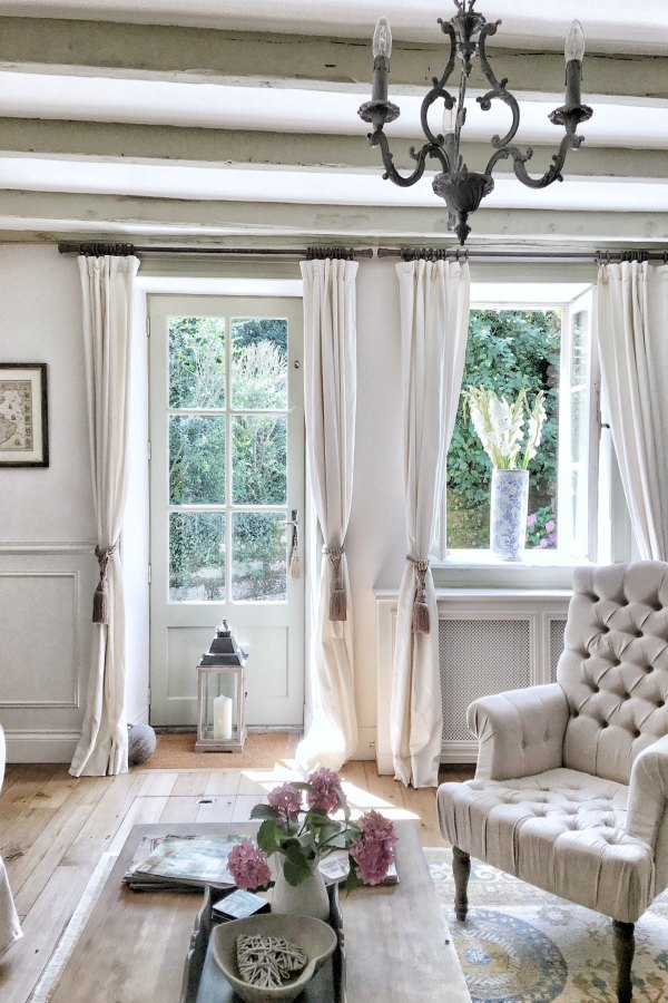 Breezy and unfussy with Belgian linen curtains from Pottery Barn, this French farmhouse living room with white (Farrow and Ball's Strong White) and French Gray accents is as timeless as it is refreshing - Vivi et Margot. Click through for Perfect Light Gray Paint Colors You'll Love as Well as Interior Design Inspiration Photos. #bestgreypaint #paintcolors