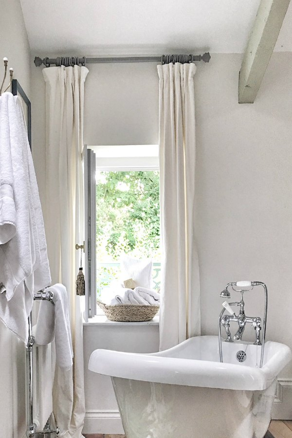 Romantic bathroom in France with clawfoot tub near window. Enjoy this house tour and ideas to get a rustic European country look!