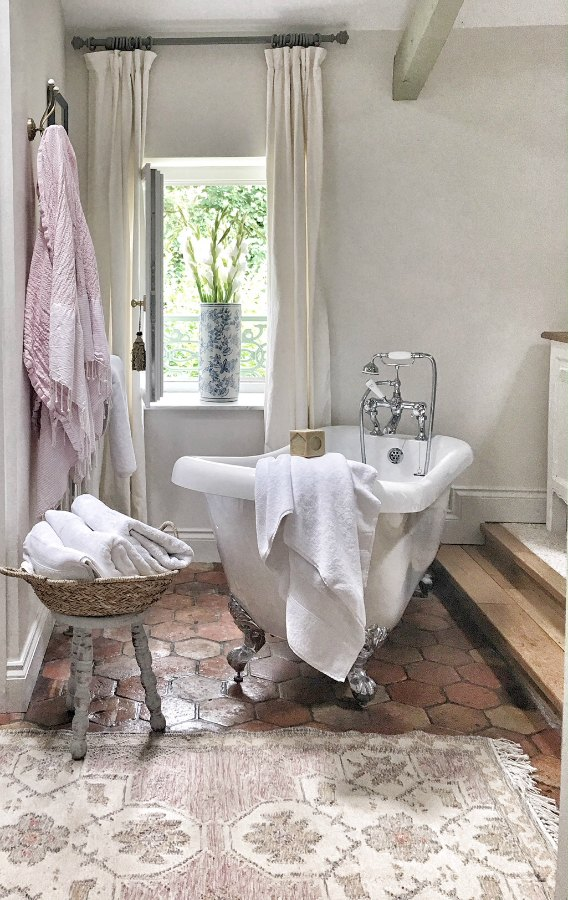 Quiet and timeless hues in a French farmhouse bathroom by Vivi et Margot features reclaimed terracotta hex tiles, freestanding tub, romantic chandelier, and Farrow and Ball's Strong White on the walls.