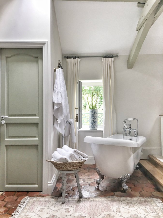French farmhouse bathroom with Farrow and Ball French Gray painted trim, Strong White on walls, clawfoot tub, beamed ceiling, and antique terracotta floor tiles. Vivi et Margot. Find the right white paint color for your own space!