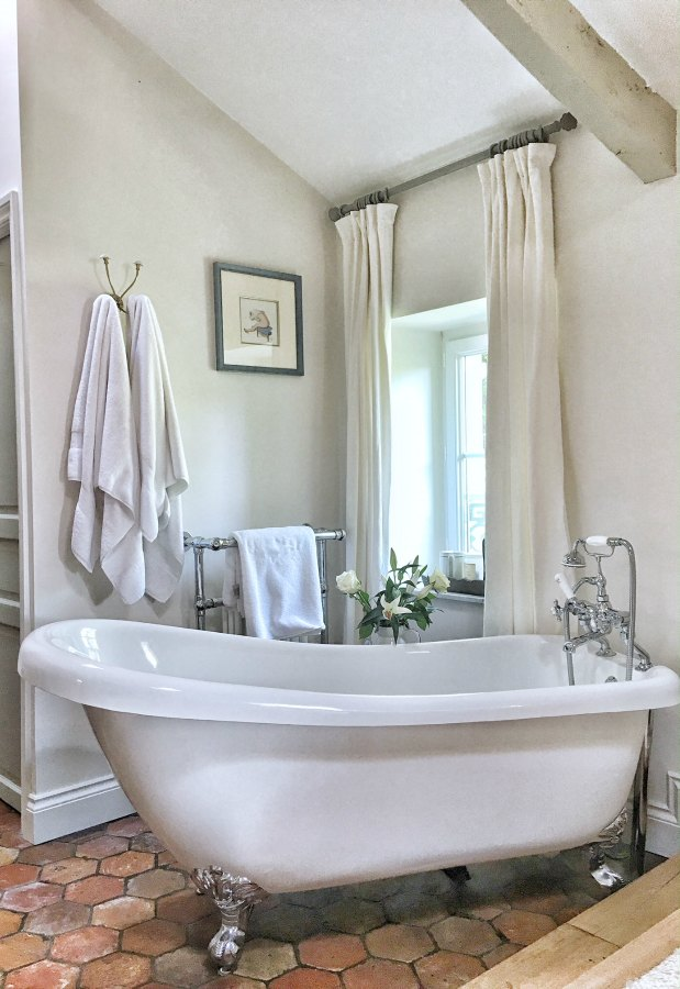 Quiet and timeless hues in a French farmhouse bathroom by Vivi et Margot features reclaimed terracotta hex tiles, freestanding tub, romantic chandelier, and Farrow and Ball's Strong White on the walls. Come score ideas for 16 Amazing Serene Paint Colors Interior Designers Use for a Soothing Vibe.