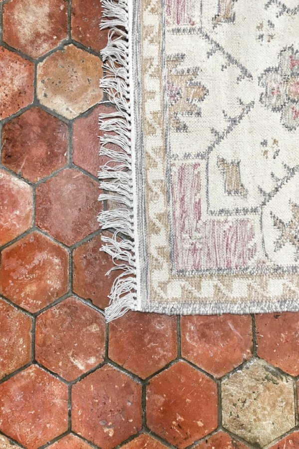 Detail of terracotta antique tiled floor with rug.