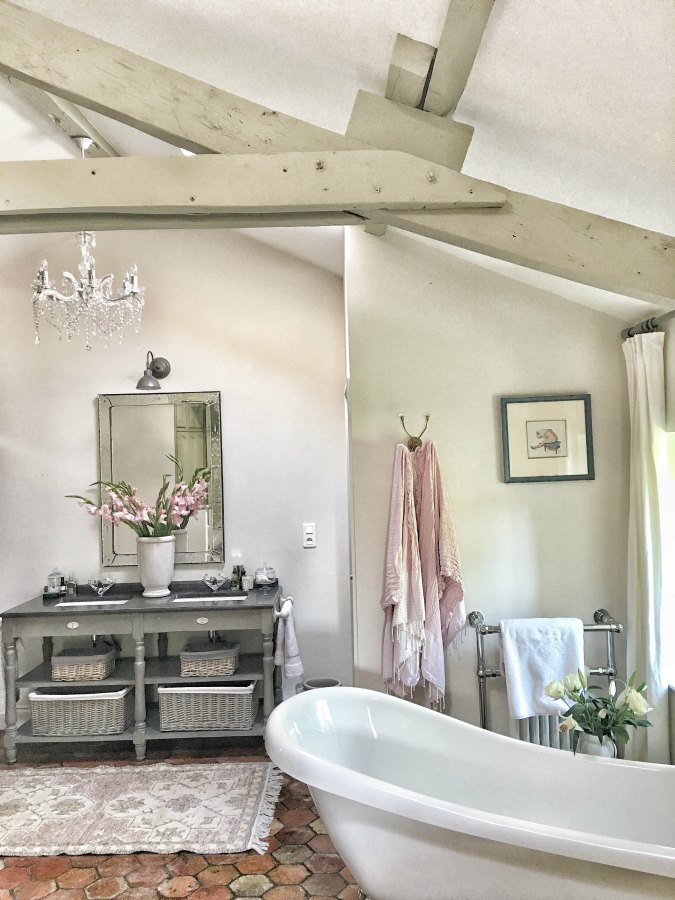 Antique hex terracotta floor tiles in a romantic bathroom in France. Enjoy this house tour and ideas to get a rustic European country look! #bathroomdesign #oldworldstyle #frenchcountry #terracottatiles