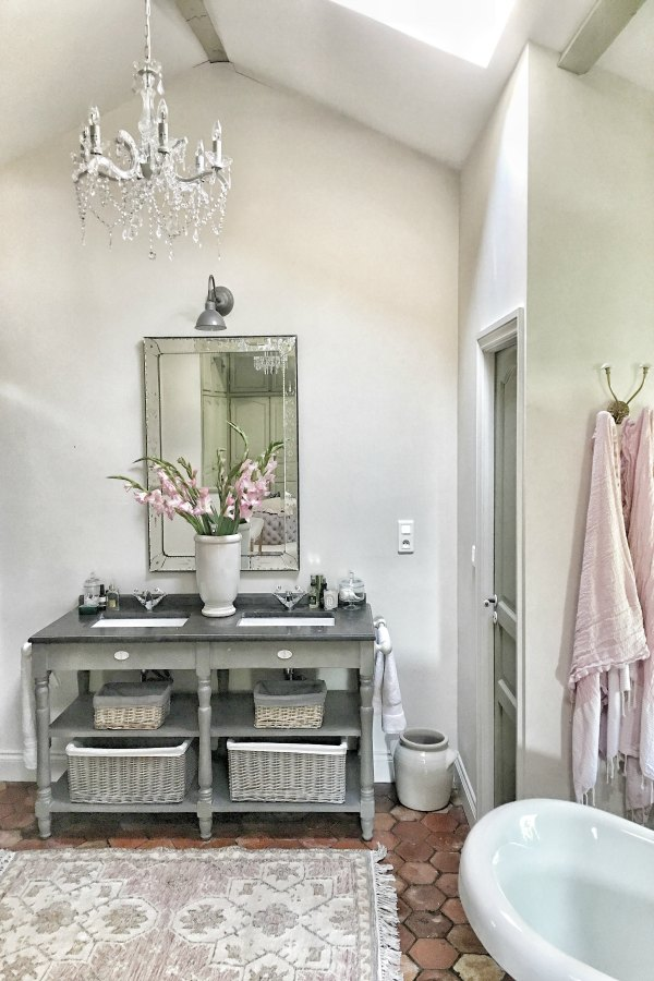 Romantic bathroom in France with crystal chandelier. Beautiful French farmhouse design inspiration, house tour, French homewares and market baskets from Vivi et Margot. Photos by Charlotte Reiss. Come be inspired on Hello Lovely and learn the paint colors used in these beautiful authentic French country interiors. #frenchfarmhouse #hellolovelystudio #frenchcountry #designinspiration #interiordesign #housetour #vivietmargot #rusticdecor #frenchhome #authentic #farrowandballfrenchgray #frenchmarket #summerhouse #europeanfarmhouse