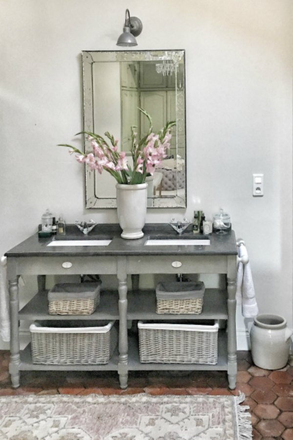 Freestanding vanity with open shelving in a rustic authentic bathroom renovated by Vivi et Margot. #bathroomdesign #bathroomvanity #frenchfarmhouse