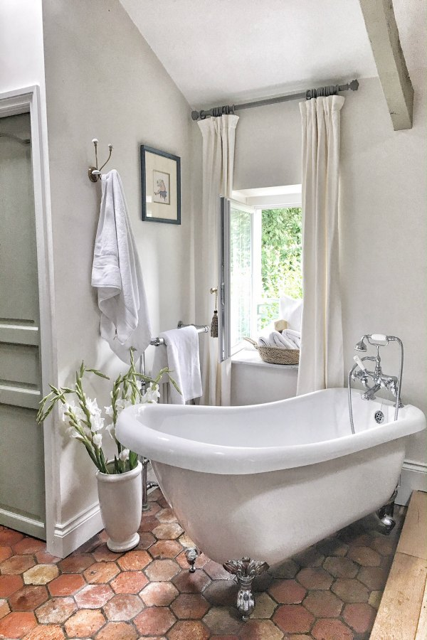 Clawfoot tub and antique terracotta tiles in bath. Enjoy this house tour and ideas to get a rustic European country look! #bathroomdesign #clawfoottub #frenchcountry #farrowandballstrongwhite