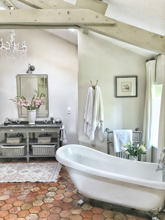Romantic bathroom with clawfoot tub and reclaimed antique terracotta floor tile in a renovated farmhouse in France by Vivi et Margot. #frenchfarmhouse #bathroomdesign #terracottatiles #interiordesign