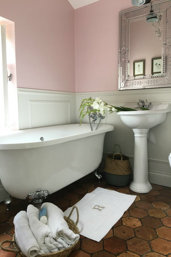Farrow and Ball Middleton Pink walls in girls bathroom in French farmhouse by Vivi et Margot. Reclaimed antique terracotta tile flooring. Clawfoot tub and pedestal sink. #bathroomdesign #farrowandball #middletonpink #clawfoottub #vivietmargot #terracottatilefloor  #frenchcountry