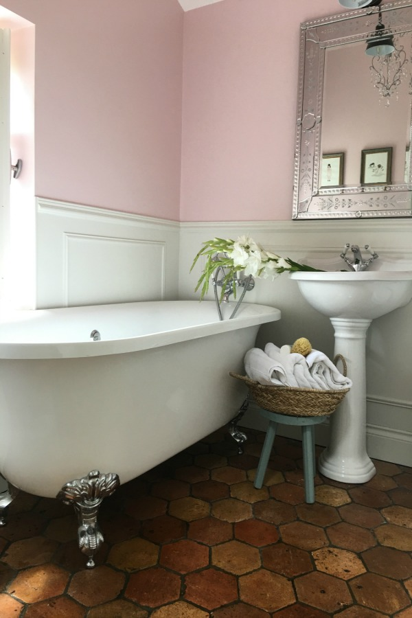 Farrow and Ball Middleton Pink walls in girls bathroom in a charming farmhouse in France by Vivi et Margot. Reclaimed antique terracotta tile flooring. Clawfoot tub and pedestal sink.Get the paint colors and design resources now!