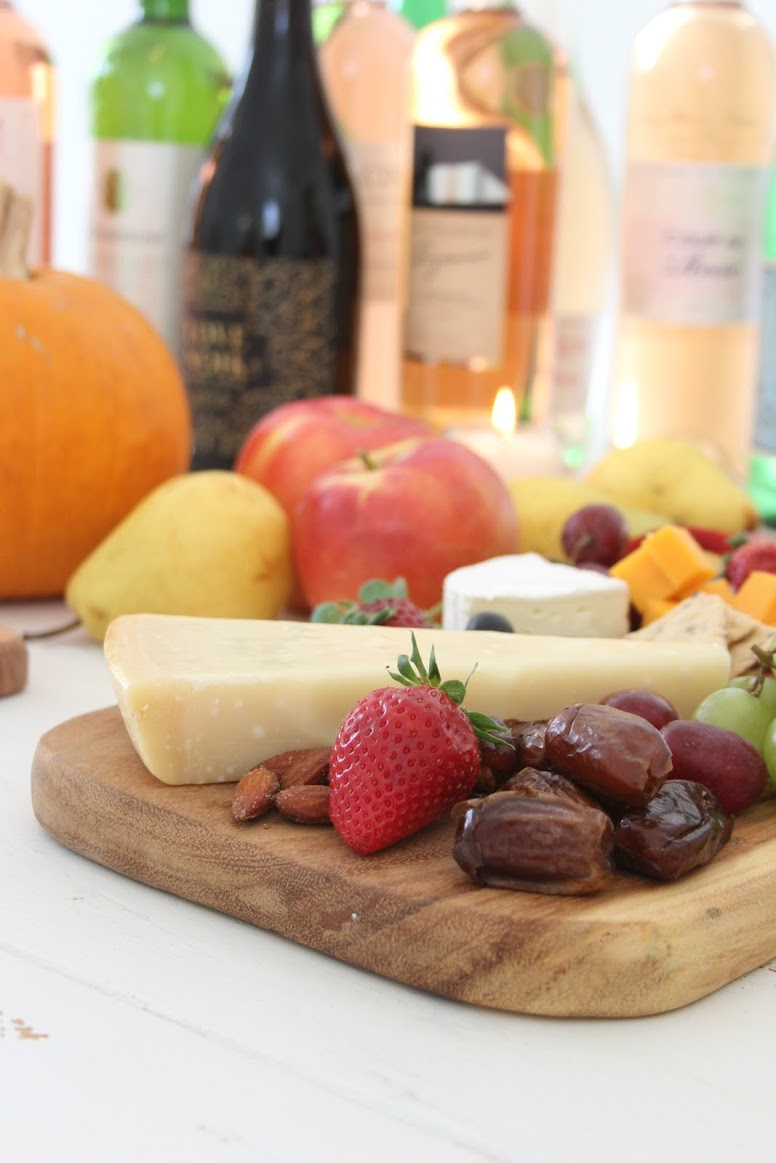 Colorful fruit and cheese for a fall tablescape. Hello Lovely Studio. #hellolovelystudio #cheeseboard #falltablescape #wineandcheese