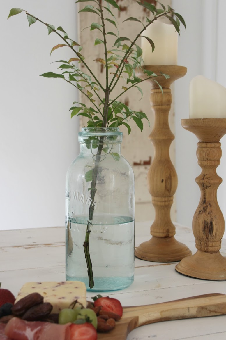Hello Lovely Studio serene vignette with branch and rustic candle holders.