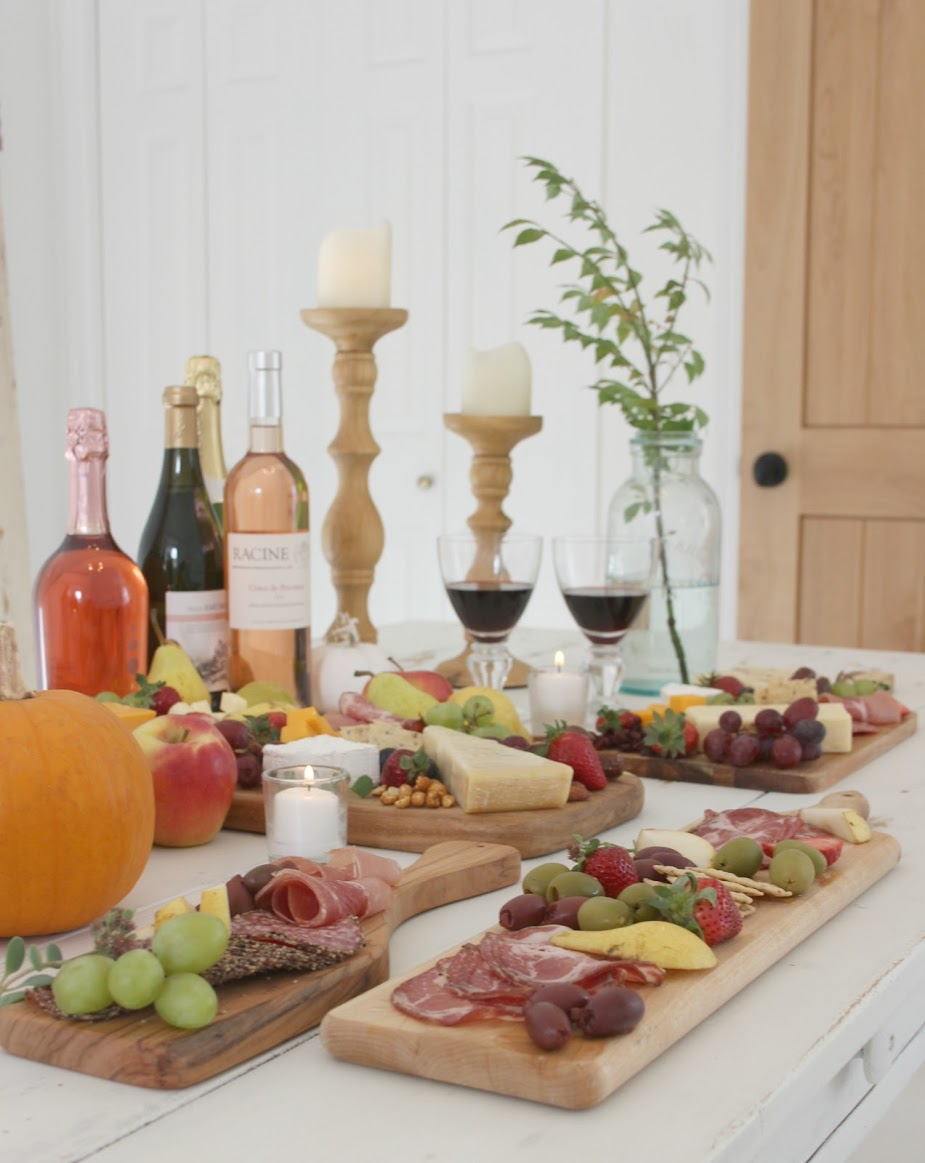 Colorful fall tablescape with cheese boards, charcuterie, and wine. Hello Lovely Studio. #hellolovelystudio #cheeseboard #tablescape #charcuterie #fallfood #falltablescape