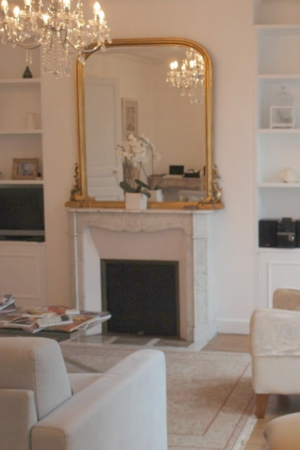 White marble surround fireplace in a Paris apartment. Hello Lovely Studio. #parisapartment #fireplace #crystalchandelier